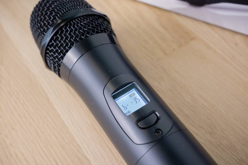 A microphone on a wooden table  Description automatically generated
